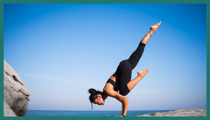 A woman balancing herself on her hands in a yoga pose
